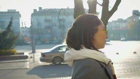 Retrato de uma moça no lado, anda em torno da cidade em um revestimento e em vidros vídeos de arquivo