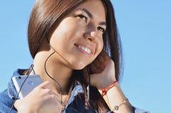 Retrato de uma moça que escute a música na rua ao andar imagem de stock royalty free