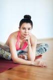 Retrato de uma moça que senta-se em um gym em um tapete, olhando no olho Imagem de Stock