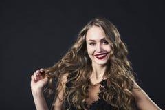 Retrato de uma moça de sorriso em um vestido do laço em um fundo preto imagens de stock