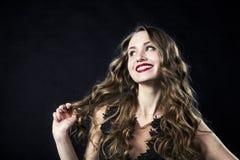 Retrato de uma moça de sorriso em um vestido do laço em um fundo preto fotografia de stock