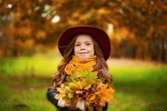 Retrato de uma moça de sorriso que esteja realizando em sua mão um ramalhete das folhas de bordo do outono imagem de stock