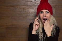 Retrato de uma moça surpreendida com um telefone celular Fotos de Stock Royalty Free