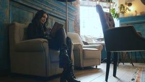 Retrato de uma morena encantador que senta-se em uma cadeira com uma tabuleta em suas mãos video estoque