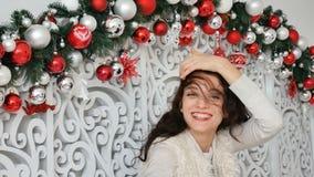 Retrato de uma morena encaracolado brilhante contra o contexto da decoração do Natal com as bolas de prata e escuras video estoque