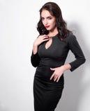 Retrato de uma mulher adulta bonita da sensualidade no vestido preto que levanta sobre o fundo branco Vista na câmera Imagem de Stock Royalty Free