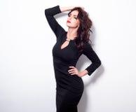 Retrato de uma mulher adulta bonita da sensualidade no vestido preto que levanta sobre o fundo branco Vista na câmera Fotos de Stock
