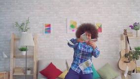 Retrato de uma mulher africana feliz com um penteado afro nos óculos de sol que jogam para fora cédulas do dinheiro video estoque