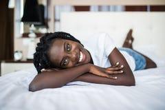 Retrato de uma mulher africana nova bonita de sorriso que relaxa na cama fotos de stock