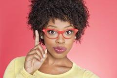 Retrato de uma mulher afro-americano em vidros retros que aponta para cima sobre o fundo colorido Foto de Stock