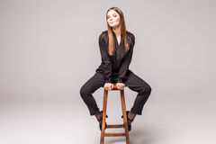Retrato de uma mulher alegre feliz no assento preto na cadeira e em olhar a câmera sobre o fundo cinzento Fotografia de Stock Royalty Free