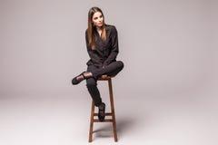 Retrato de uma mulher alegre feliz no assento preto na cadeira e em olhar a câmera sobre o fundo cinzento Imagem de Stock Royalty Free
