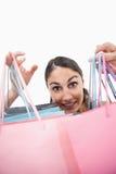 Retrato de uma mulher alegre que mostra sacos de compra Fotografia de Stock