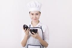 Retrato de uma mulher asiática no uniforme do cozinheiro chefe que guarda uma bacia de arroz Imagens de Stock