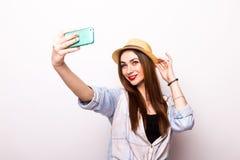 Retrato de uma mulher atrativa nova com o chapéu que faz a foto do selfie Foto de Stock Royalty Free