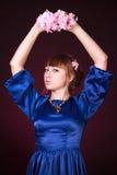 Retrato de uma mulher atrativa nova em uma obscuridade - dres azuis da noite Imagens de Stock