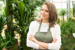 Retrato de uma mulher atrativa nova no berçário das plantas Foto de Stock
