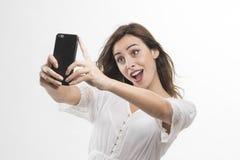 Retrato de uma mulher atrativa nova que faz a foto do selfie no smartphone foto de stock royalty free