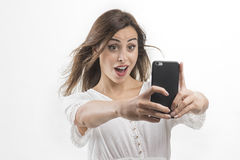 Retrato de uma mulher atrativa nova que faz a foto do selfie no smartphone fotos de stock