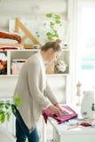 Retrato de uma mulher atrativa que trabalha com um teste padrão da costura imagem de stock royalty free