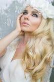 Retrato de uma mulher bonita com cabelo louro longo e os olhos verdes que se está sentando atrás da janela de vidro e sorri graci Imagem de Stock Royalty Free
