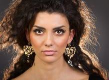 Retrato de uma mulher bonita com seus brincos Imagens de Stock Royalty Free
