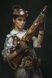 Retrato de uma mulher bonita do steampunk que guarda uma arma foto de stock