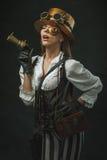 Retrato de uma mulher bonita do steampunk que guarda uma arma fotos de stock