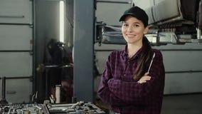 Retrato de uma mulher bonita e segura que guarda uma chave de impacto ao trabalhar como o auto mecânico em um moderno vídeos de arquivo