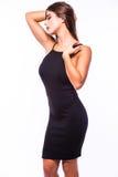 Retrato de uma mulher bonita em pouco vestido preto da forma no fundo cinzento Fotografia de Stock