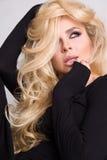Retrato de uma mulher bonita em um fundo branco e em um cabelo louro encaracolado longo e uma boca sensual com chicotes longos, v Fotos de Stock Royalty Free