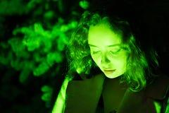 Retrato de uma mulher bonita misteriosa na iluminação verde com fundo verde imagens de stock