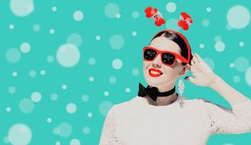 Retrato de uma mulher bonita no equipamento e nos óculos de sol do Natal com os bordos pintados brilhantes fotografia de stock