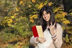 Retrato de uma mulher bonita no parque do outono, guardando um livro Foto de Stock