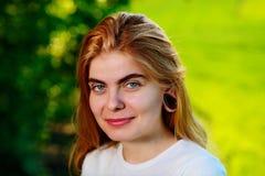 Retrato de uma mulher bonita nova com túneis de madeira em seu e fotografia de stock