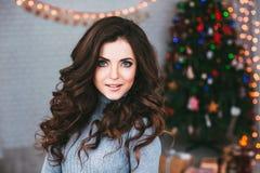 Retrato de uma mulher bonita nova em decorações obscuras de um Natal do fundo Fotos de Stock Royalty Free