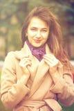 Retrato de uma mulher bonita nova no revestimento bege Imagem de Stock