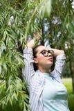 Retrato de uma mulher bonita nova nos vidros, em uma natureza verde do verão do fundo Foto de Stock Royalty Free