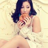 Retrato de uma mulher bonita nova que come seu croissant francês foto de stock
