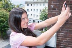 Retrato de uma mulher bonita nova que toma um selfie foto de stock royalty free
