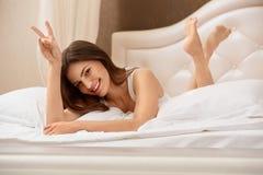 Retrato de uma mulher bonita que relaxa na cama Imagens de Stock Royalty Free