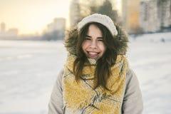 Retrato de uma mulher caucasiano nova bonita em uma posição feita malha do chapéu e do lenço em um fundo do inverno com sorriso d fotos de stock