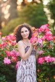 Retrato de uma mulher caucasiano nova perto do arbusto de rosas vermelho e cor-de-rosa em um jardim de rosas, olhando à câmera fotografia de stock