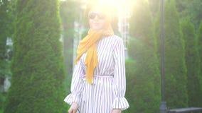 Retrato de uma mulher cega bonita nova em um hijab com um bastão fora em um dia ensolarado video estoque