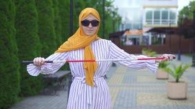 Retrato de uma mulher cega bonita nova em um hijab com um bastão no parque filme