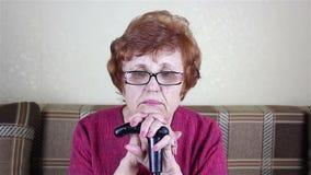 Retrato de uma mulher com óculos idosa Sits que inclina-se em uma vara de passeio video estoque