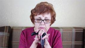 Retrato de uma mulher com óculos idosa Sits que inclina-se em uma vara de passeio filme