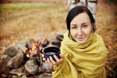 Retrato de uma mulher com uma caneca de chá quente em seu outono das mãos em uma fogueira da floresta Um piquenique na menina da  Fotografia de Stock Royalty Free