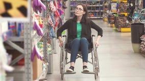 Retrato de uma mulher com uma inabilidade que veste em uma cadeira de rodas na alameda video estoque