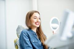 Retrato de uma mulher com sorriso saudável no escritório dental imagens de stock royalty free